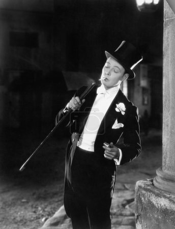 Young man in formal clothing lighting his cigarette with his walking stick