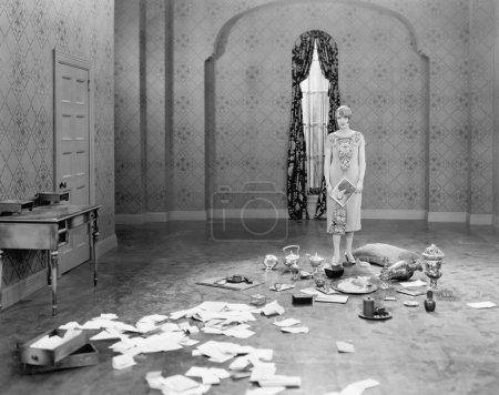 Photo for Woman standing in an empty room scattered with letters - Royalty Free Image