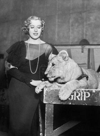 Elegant woman standing next to a lion