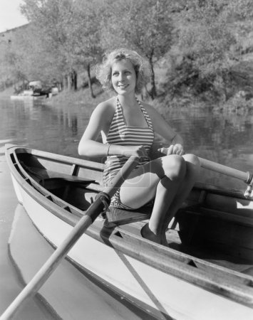 Woman in a striped bathing suit rowing