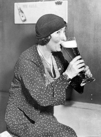 Woman drinking out of a big beer glass
