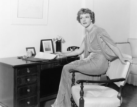 Woman in a evening dress sitting on the armrest of a chair