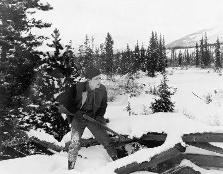 Photo pour Chasseur avec son fusil marchant dans la campagne enneigée - image libre de droit