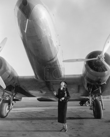 Woman standing under a large aircraft looking up