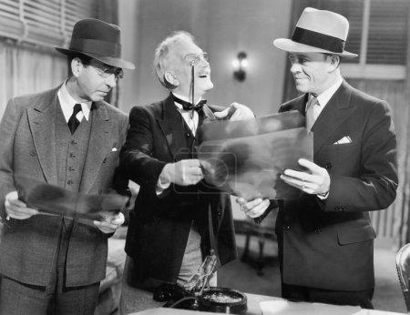 Three men looking at x-rays