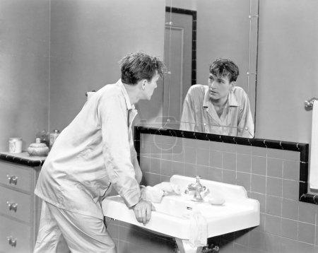 Man in bathroom looking into mirror