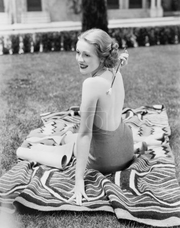Young woman sitting in a sun suit on a lawn scratching her back
