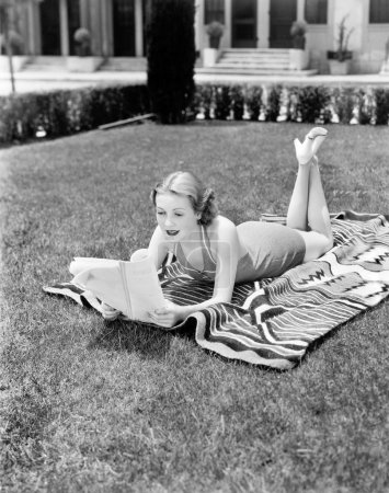 Young woman lying on a towel in her yard sunbathing and reading