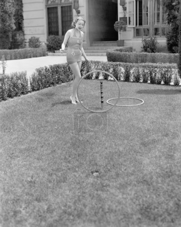 Young woman in a sun suit playing with rings in the yard