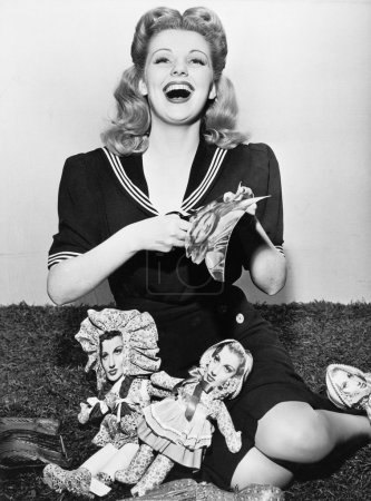 Young woman sitting and cutting out paper dolls
