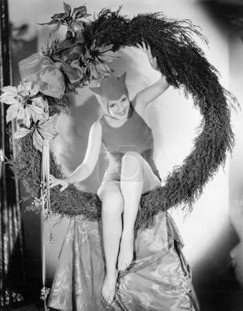 Circling in on the devil, a young woman sits in a wreath