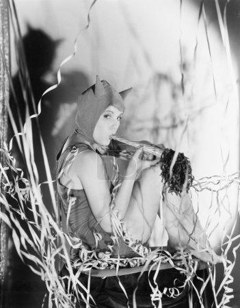 Photo pour Un diable de fête, une jeune femme souffle sa propre corne - image libre de droit
