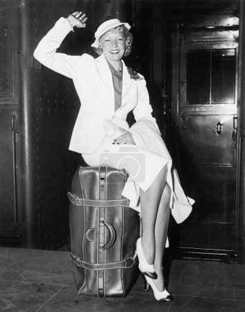 A ready to go young woman sitting on her suitcase and waving