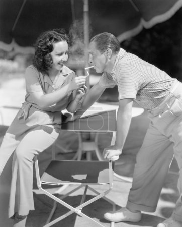 Woman giving a man a light for his cigarette
