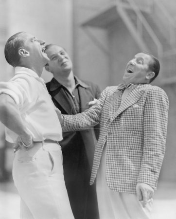 Three men standing together and laughing