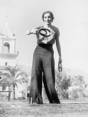 Young woman in a yard, playing horse shoes, aiming for a lucky toss