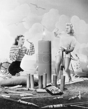 Two women sitting around fire works