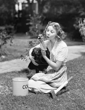 junge Frau mit Axt neben sich umarmt einen Truthahn