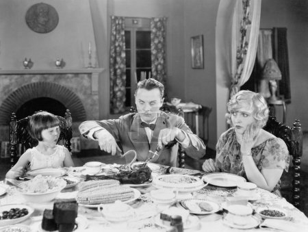 Family of three sitting together having dinner