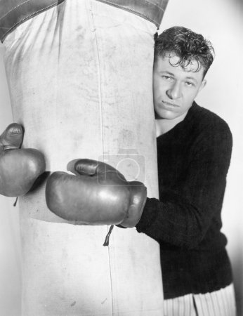 Man in boxing gloves hugging the punching bag