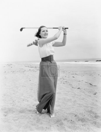 Young woman playing golf at the beach