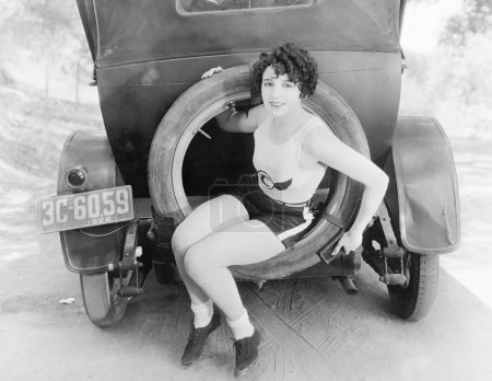 Young woman sitting in the extra wheel of a car