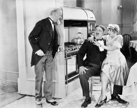Photo pour Jeune femme de ménage assise sur les genoux de son amant dans la cuisine - image libre de droit