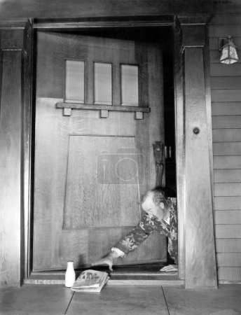 Man crawling at the front door to reach his newspaper and milk