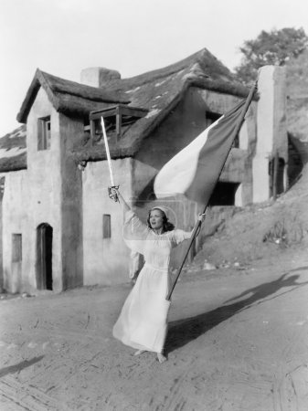 Young woman walking with a flag and a sword