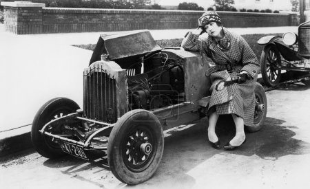 Young woman sitting next to small car looking at the engine in disbelieve