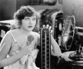 Young woman sitting next to a fan and a thermometer looking hot and eating an ice cream