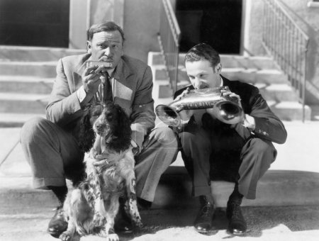 Two men playing two harmonicas with an English Setter