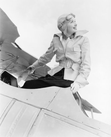 Young woman sitting on top of a biplane with gargles and hat