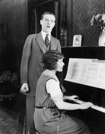 Man singing and woman playing the piano