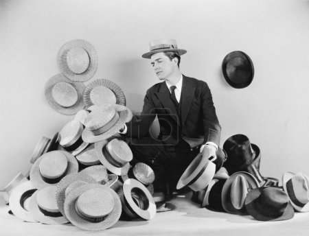 Man sitting on the floor surrounded by hats