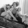 Three women sitting on top of a piano...