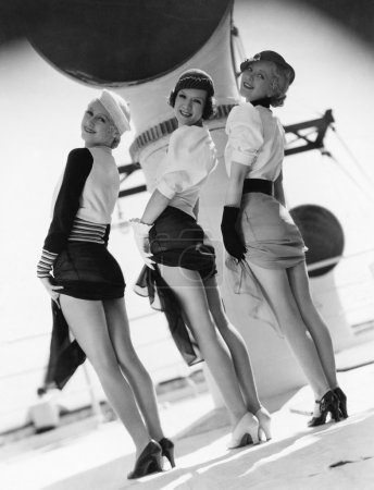 Three women looking over their shoulders and showing their legs