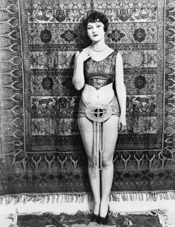 Young woman barely dressed in front of a hanging carpet