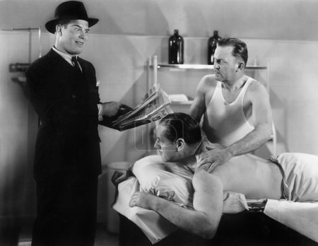 Well dressed man reading to a man who is getting a massage