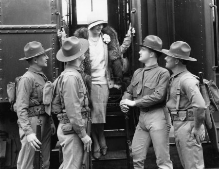 Woman being greeted by four soldiers