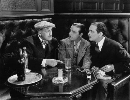 Three men sitting together at a bar