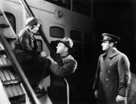 Two men talking to a young woman sitting on the ship's step