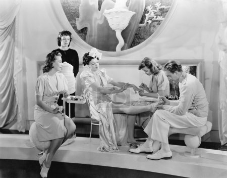 Young woman being pampered by three women and a man