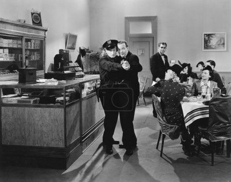 Policeman and a man dancing a tango in a restaurant