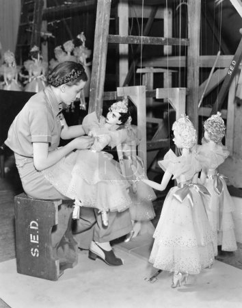 Young woman working with puppets on a string