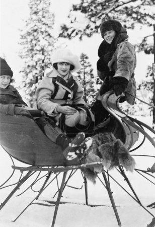 Photo pour Trois femmes assises dans un traîneau - image libre de droit