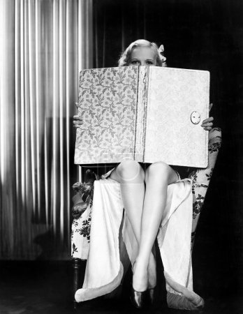 Photo for Young woman looking over top of an oversized book - Royalty Free Image