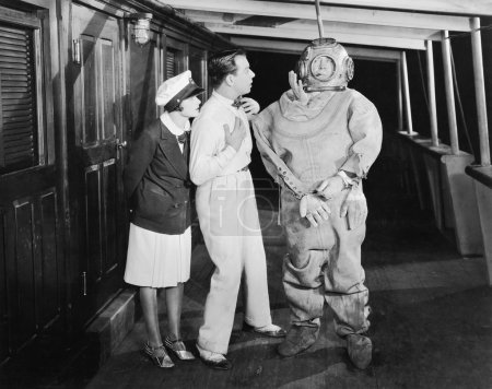 Two looking in shock at a diver in a divers suit