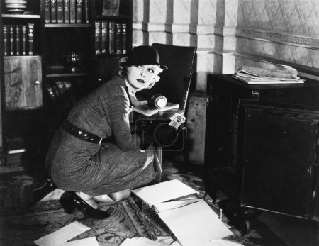 Young woman in an office next to a safe, looking over her shoulder