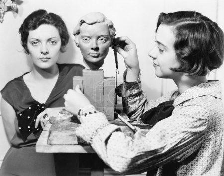 Les femmes et un artiste debout ensemble pendant qu'on travaille sur un buste
